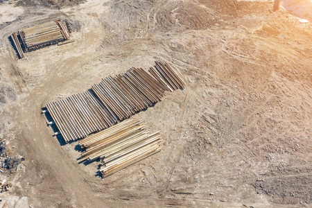 Construction piles lie on the ground, for the construction of the house, aerial view.