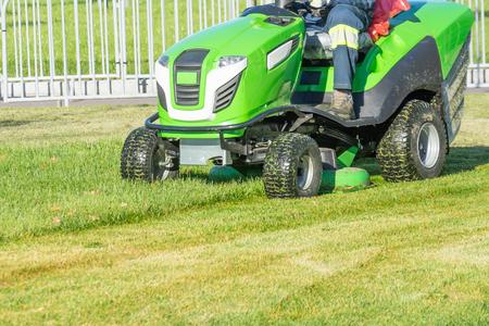Ride lawn mower mows a green fresh grass