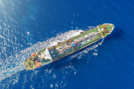 Ship, with bulk cargo, sails in the blue sea. Aerial view