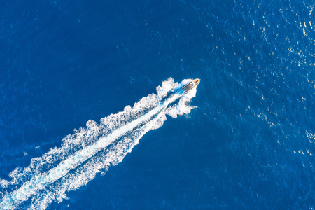 Boat launch at high speed floats in the Mediterranean, aerial top view 免版税图像