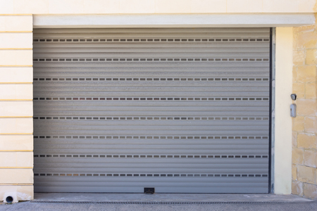 Automatic gray garage door, closed, with a bell at the door