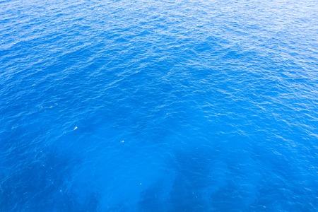 Niebieska woda morska z małymi falami i gradientowym kolorem tła Zdjęcie Seryjne