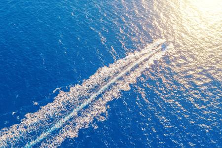 Lanzamiento del barco a alta velocidad flota a la luz del sol en el Mediterráneo, vista aérea superior Foto de archivo