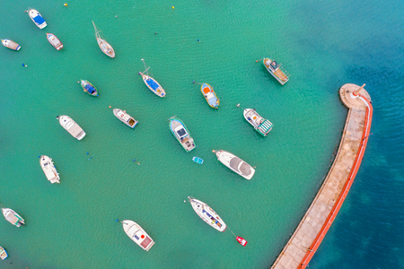 Aerial view of the bay with turquoise water and many small fishing boats with jetty and lighthouse Imagens