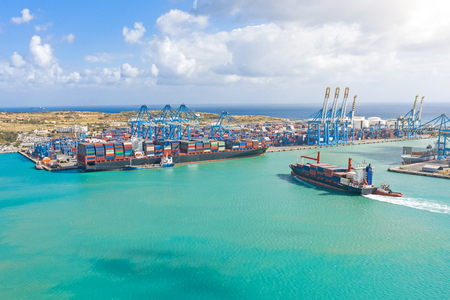 Luftbild aus der Höhe eines Frachthafens in einem Frachtseehafen, ein Segelschiff mit Containern und ein weiteres über die Verladung von Gütern Standard-Bild