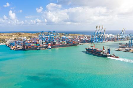 Vue aérienne depuis la hauteur d'un port de fret dans un port maritime de fret, un voilier avec des conteneurs et un autre sur le chargement de marchandises Banque d'images