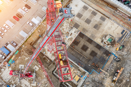 Installation of a construction crane, with the help of a crane on a truck, aerial top view of the pit and building site, the foundation