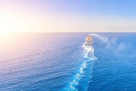 Cruise ship liner goes into horizon the blue sea leaving a plume on the surface of the water seascape during sunset. Aerial view, concept of sea travel, cruises 免版税图像