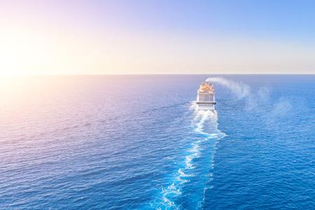 La nave da crociera entra nell'orizzonte del mare blu lasciando un pennacchio sulla superficie del paesaggio marino dell'acqua durante il tramonto. Vista aerea, concetto di viaggio in mare, crociere