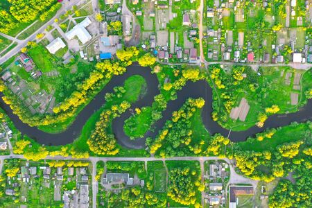 Aerial view landscape of winding small river among the small town, stream in green field Standard-Bild