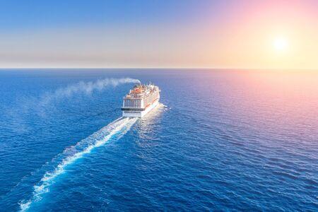 Le paquebot de croisière entre à l'horizon de la mer bleue, laissant un panache à la surface du paysage marin pendant le coucher du soleil. Vue aérienne, concept de voyage en mer, croisières