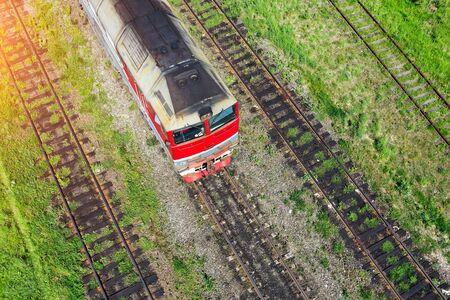Four railway tracks and a red locomotive on one of them Stockfoto