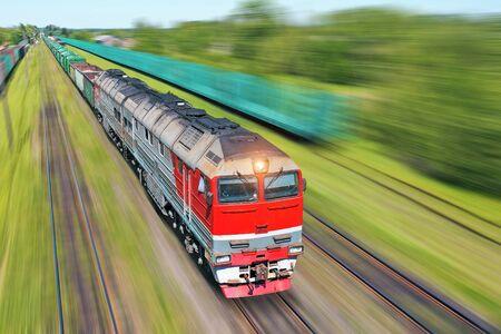 Treno merci che va in fretta lungo il treno ad alta velocità. Concetto di trasporto ferroviario
