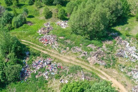 Large landfill of garbage, household waste, plastics and other things among the green forest along the meadows and the road. Aerial view from above drone