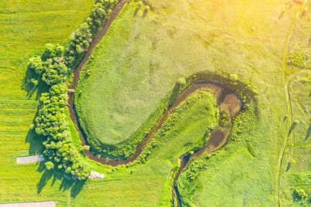 Aerial landscape countryside of winding small river, stream in green field, top view sunset meadow