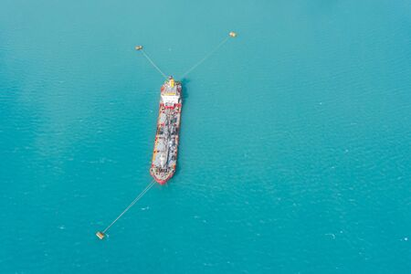 Aerial view of tanker fuel ship moored in a port bay to buoys