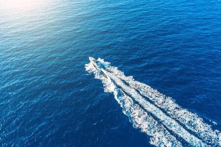 Boat launch at high speed floats to sunlight in the Mediterranean, aerial top view