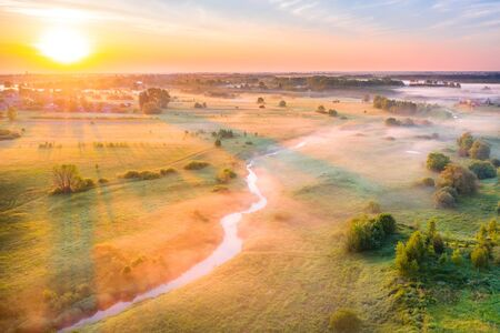Aerial view of the morning mist above the ground among a small river of meadows of fields, the sun illuminates the tree and casts a long shadow