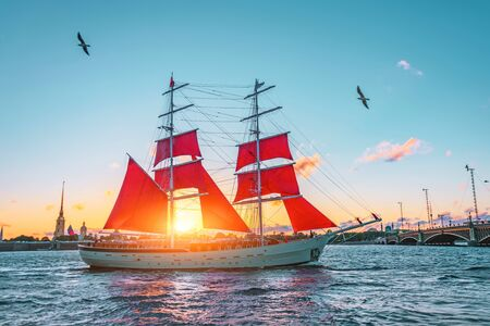 Scarlet sails in St. Petersburg on the Neva River, sunset at the divorced bridge