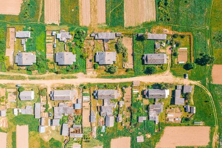 Aerial view from the height of the village with houses and streets, plowed fields, meadows in the summer