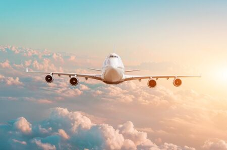 Large passenger plane with four engines flies in the sky at sunset Stock Photo