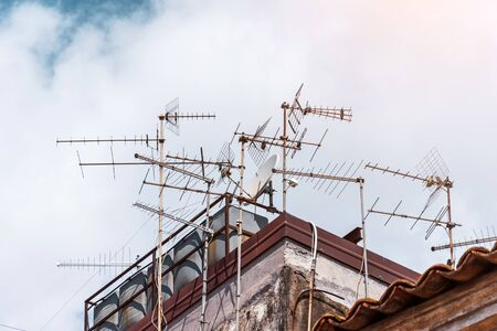 Many antennas of satellite and analog television on the roof building 免版税图像 - 126031652