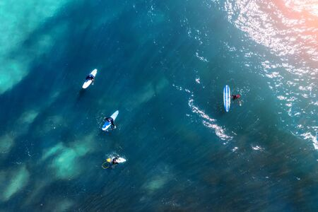 Surfers on the water in the bay in anticipation of a big wave, aerial top view Stock Photo