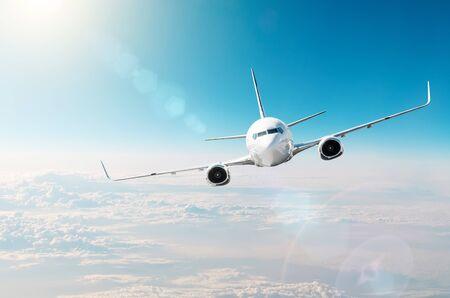 El avión realiza un giro alto en el cielo sobre el sol brilla reflejando la luz del resplandor Foto de archivo