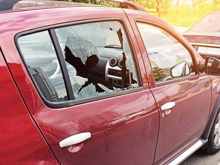 Glasscherben an der Beifahrertür eines geparkten Pkw. Das Konzept der Kriminalität von Autodiebstahl, Diebstahl von Wertsachen