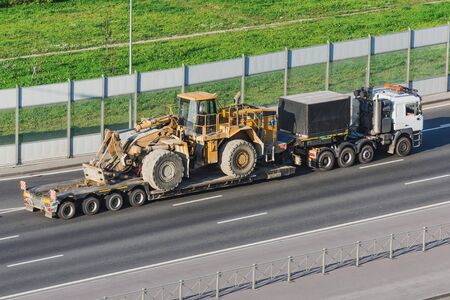 Truck with a long trailer platform for transporting heavy machinery, loaded big tractor with bucket. Highway transportation