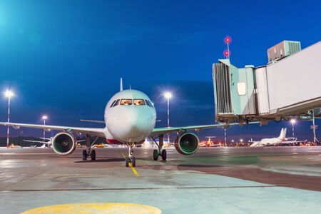Passenger aircraft arrives at the terminal by night flight, gangway waiting for disembarking passengers