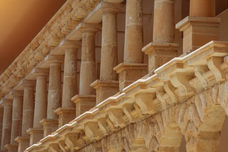 low columns of orange limestone stone, elements of external architecture