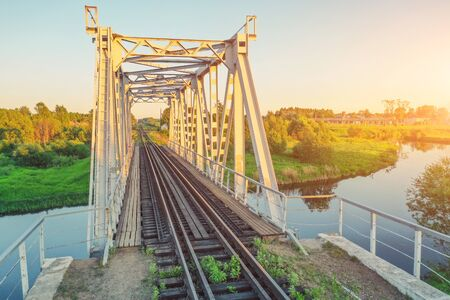 Railway bridge over a small river, sunset view Фото со стока