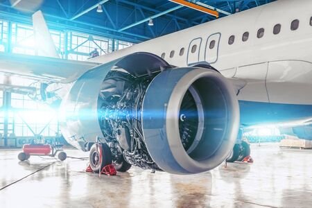 Industrial theme view. Repair and maintenance of aircraft jet engine with hood open on the wing