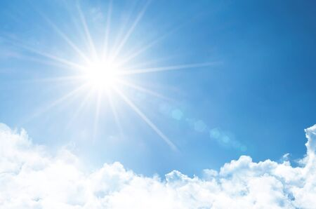 Clear sky with bright sun and rays in the atmosphere, below are light fluffy clouds