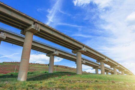 Puente de la carretera de giro de dos carreteras, soportes de viaductos en el valle entre las colinas verdes, infraestructura de transporte Foto de archivo