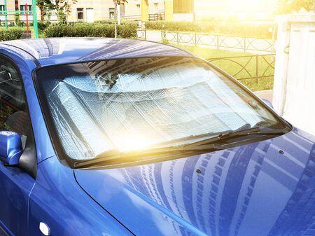 Superficie riflettente protettiva sotto il parabrezza dell'autovettura parcheggiata in una giornata calda, riscaldata dai raggi del sole all'interno dell'auto Archivio Fotografico