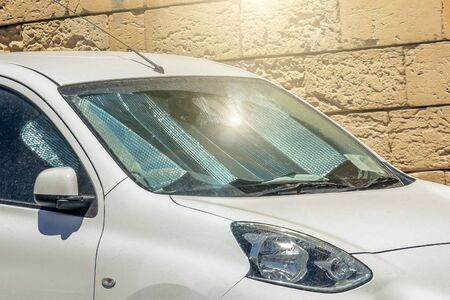 Protective reflective surface under the windshield of the passenger white car parked on a hot day, sun rays protection and heating vehicle interior. Stok Fotoğraf