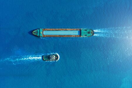 Cargo ship barge and tugboat sail to meet each other in the seaport of the port, aerial view Reklamní fotografie