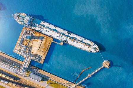 Aerial top view tanker at unloading in a large bulk port liquid cargo, oil, liquefied gas, fuel.