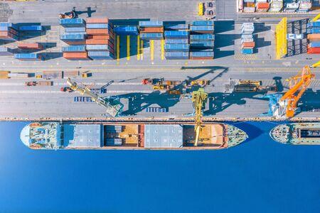Luftbild von oben riesiges Frachtschiff vertäut am Pier im Hafen, Verladen von Waren, Metall, Beton und anderen festen Rohstoffen