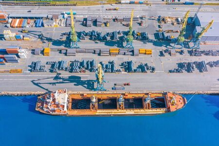 Aerial top view huge cargo ship moored at the pier at the port, loading goods, metal in aluminum rolls, concrete and other solid raw materials.