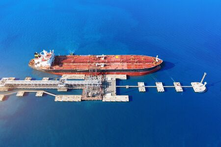 Aerial view large port oil loading terminal with large storage tanks. Railway infrastructure for the delivery of bulk cargo by sea, using pump station in ship tanker for transportation and delivery Stock Photo