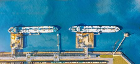 Aerial top view wide panorama of the oil terminal and two moored tankers with liquid fuel loaded on the pier, railway tank cars for loading and unloading