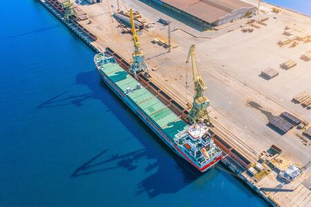 Aerial top view huge cargo ship moored at the pier at the port, loading goods, ore mineral bulk cargo in railway cars, concrete and other solid raw materials Reklamní fotografie
