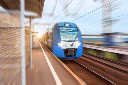 Tren eléctrico a alta velocidad pasa por la estación de la plataforma de pasajeros en la ciudad Foto de archivo
