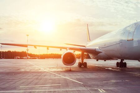 View of the wing and engine of a long-range passenger aircraft, evening airport at sunset