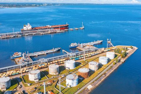 Aerial view large port oil loading terminal with large storage tanks. Railway infrastructure for the delivery of bulk cargo by sea, using pump station in ship tanker for transportation and delivery Banco de Imagens