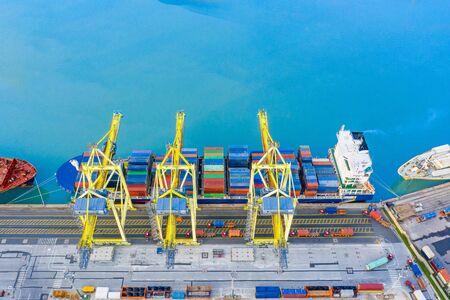 Großes Frachtschiff im Hafen liegt im Hafen, Kräne laden Fracht von LKWs, die Container liefern, Luftaufnahme von oben