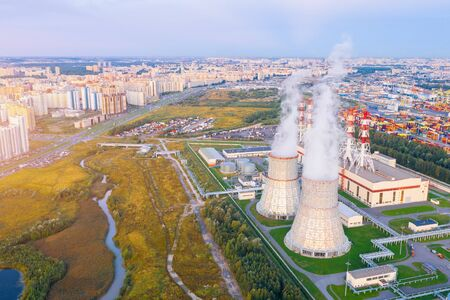 City thermal power station close to massive residential areas in the evening before sunset, aerial view